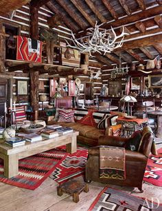 In the adjacent saloon, a vintage English club chair and a sofa covered in a Ralph Lauren Home leather are grouped with a bespoke cocktail table atop antique Navajo rugs.
