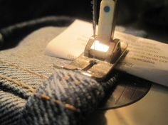 ( Sewing tips  thick seams broken needles denim ) Closeup of folded paper under rear of presser foot.