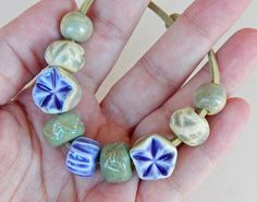 The set consists of =9 beads of porcelain ,hand carved ,have blue and green glazes . By Mª Carmen Rodriguez Martinez ( Majoyoal )  https://www.facebook.com/groups/CeramicArtBeadMarket