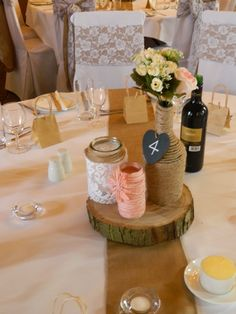 Lovely twined bottle & jam jars on top of a tree trunk slice.(simple but very effective)  www.blueorchid-events.com
