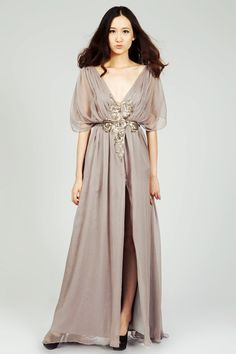 Flirt the night away with this countdown cool and updown appealing grey crepe wrap evening dress. It features bold deep v-neck and dramatic kimono sheer half sleeves. Thigh-high split exude an ethereal nymphlike glam. Simple, yet the appliqued sequins do so much. Snap button closure at front.