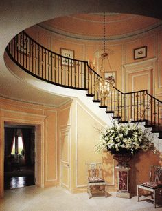 Henri Samuel had the entrance hall painted salmon. A Languedoc marble jardiniere from Versailles stands bewteen two Indian chairs in ivory.