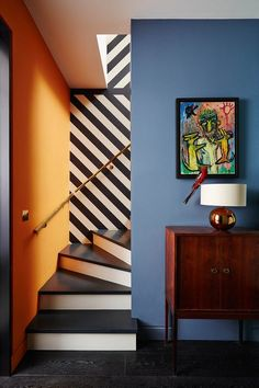 Suzy designed the black-and-white striped wallpaper that spirals down along the staircase from the kitchen to the basement's work den and cinema room. Suzy Hoodless