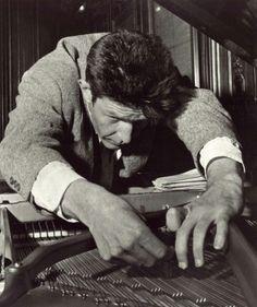 John Cage preparing a piano