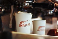 Effective red stamped branding on white coffee cups. Godshot coffee, Berlin.