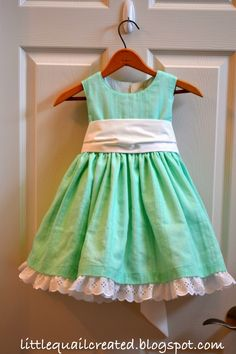 I like the eyelet lace peeking out from under the dress and the wide sash.