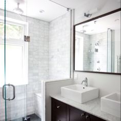 Frameless shower door, dark millwork, subway tiles, bench seat and showerhead in ceiling instead of projecting from wall