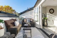 terrasse tropézienne aménagée avec un salon de jardin en résine tressée et décorée d'un tapis extérieur à chevrons