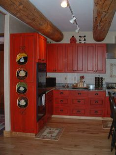Bright red distressed cabinets with black accent glaze