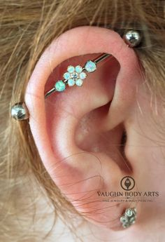 Implant grade titanium barbell with three holes drilled in the shaft, 3mm prong set white opal accents, and center stage, a stunning white opal and CZ flower set in 18k yellow gold. All jewelry by anatometal​. Thanks so much, Brianna! It looks absolutely stunning. vaughnbodyartsMonterey, CA