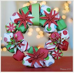 Christmas Origami Paper Wreath at Dollar Store Crafts (couldn't you wrap small boxes and make a present-wreath?!)