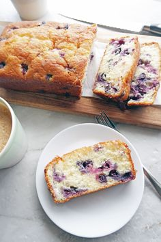 A slice of fluffy Classic Lemon Blueberry Loaf Cake on a white plate; the remaining loaf cake on a long wooden board in the background.