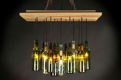 Rough, reclaimed wood is the ideal contrast against spectacular illumination, and this Wine Bottle Chandelier combines the two worlds. Reclaimed wood and reclaimed wi. Recycled Wine Bottles, Lighted Wine Bottles, Bottle Lights, Wine Bottle Crafts, Glass Bottles, Wine Bottle Chandelier, Hanging Light Fixtures, Wood Design, Home Lighting