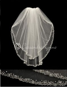 This two tier wedding veil is standard cut with a scrolling silver embroidery design. The design is complimented with silver lined seed beads and rhinestones. I