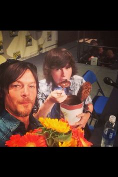 """Chandler Riggs and Norman Reedus. can i just point out that Norman is holding flowers? """"Look at the flowers"""""""