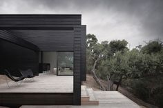 Ridge Road Residence by StudioFour, located in Fingal, Australia. The black timber clad exterior is combined with  dark reflective glass, with a strong indoor-outdoor connection.