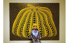 Yayoi Kusama in front of a painting from the Pumpkin series, 2004