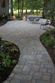 This lovely pavingstone walkway opens up to a lovely backyard patio.