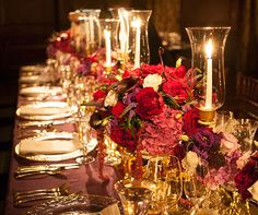 The glow of tapers in trumpet hurricanes illuminates sizable floral arrangements of calla lilies, amaranthus and roses.