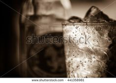 A glass of soda water with ice in sepia tone.Toned image,soft focus,film noir style.