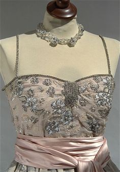 Micol Fontana - 1955 Detail gown evening gowns, pale pink, strapless neckline with rhinestones. The full skirt is embellished with floral motifs with applied leaves embroidered in silver and iridescent sequins, beads in Venice and canette.  Fabric: silk organdy work. Created by Jacqueline Bouvier Kennedy.