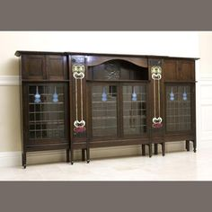 Charles Rennie Mackintosh - Bookcase. Oak,Ceramic Inlays, Brass, Pewter, Enamel, & Leaded Glass. Circa 1895. 300cm x 161.5cm x 43cm.