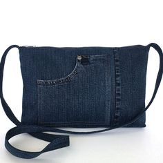 When you are on the go,this perfectly sized crossbody bag wont slow you down. I used a retired blue jean pant for the exterior of this Eco friendly bag. It features two exterior pockets, one interior pocket, and top zipper closure, This bag is fully lined with a cotton blend striped fabric.  Measurements: width: 12.5 height: 8.5 depth: 1.5 strap: 45.5 Machine washable (cold water) and dry able  see more recycled jean bags…