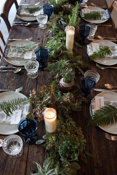 a rustic table is paired beautifully with earthy elements like ferns, berries and deep blue accents.