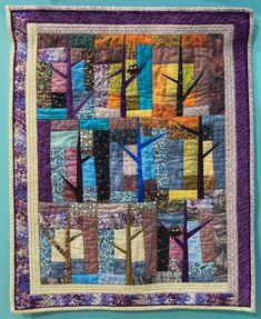 """Wall Quilt 7, """"Sunlight in a Snowy Wood"""" by Jane Kazmer  """"The original trees were started in purples and blues. While doing a jigsaw puzzle, I saw a picture of a snowy wooded area with sunlight streaming through the trees. That was the inspiration to make some more tree blocks, adding white for snow and golds for the light. The borders continue the theme of a snowy ground and darker woods. This is my first time hand quilting. Can you find the owls?"""" Snowy Woods, Hand Quilting, Capital City, Dark Wood, Sunlight, Owls, Jigsaw Puzzles, Blues, Quilts"""