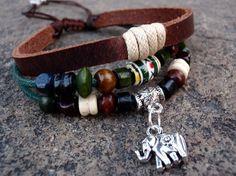 Fully adjustable multi-strand bracelet has 3 strands, they are embellished with a silver elephant charm, colorful wooden beads, various shapes of brown wooden beads, a center handmade colorful glass bead as well as suede wraps in teal . The slide knot in the back makes this fully adjustable to fi...