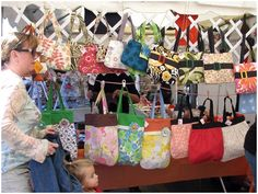 """This is a great way to display accessories & bags! I love how they line the booth and use items you may have around the house to hand from. It keeps them off tables and allows the buyers to walk into the booth with more ease. It also adds color to your """"walls!"""""""