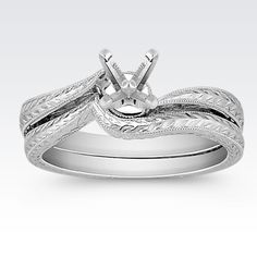 A uniquely engraved, vintage inspired design gives this intricate wedding set style and elegance. This wedding set is crafted from superior quality 14 karat white gold. This piece's delicate feminine lines create the perfect backdrop for the center diamond of your choice.
