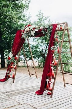 Two ladders lined with small vases are joined by red velvet for a dramatic theatrical effect / http://www.deerpearlflowers.com/fall-red-wedding-ideas/