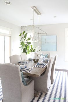 A coastal inspired tablescape with navy blue and white striped placemats, blue p… Linen Dining Chairs, Dining Room Furniture, Dining Rooms, Dinning Table, Furniture Design, Elegant Dining Room, Dining Room Design, Driftwood Table, Driftwood Chandelier