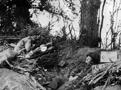 Cpl. Raymond C. Slack, left, of Milwaukee, Wis., keeps sharp lookout for German patrols at an American outpost near Saint-Lô  on july 15, 1944, while his buddy S/Sgt. Eugene Schmitz, of Roseland, Neb., tries to make up a little of the sleep he has lost while on active duty.