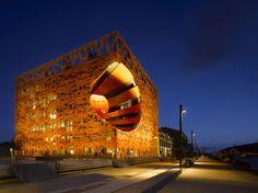 Lyon, Frankreich  Architekten: Jakob + MacFarlane  Der orange leuchtende Würfel am Ufer der Saône in Lyon sieht aus wie ein riesiges Kleinkind-Spielzeug, aber es handelt sich hier tatsächlich um ein Büro- und Kulturzentrum. Ein riesiges Loch führt orthogonal durch das Bauwerk und versorgt so die Mitte mit Tageslicht und dient außerdem als natürliche Lüftung. Eine Erdwärmepumpe und Photovoltaik-Module sorgen für eine makellose Energiebilanz des Gebäudes.