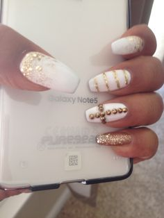Coffin shaped nails, with snowy white gel polish. Love the designs in gold.