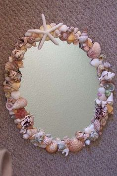 Mirror embellished with sea shells. Place candles on or hang these around your reception to reflect light!