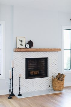 Corner Lot Modern Farmhouse Fireplace Tile Fireplace chevron marble mosaic tile A fireplace with chevron marble mosaic tile and beam mantel is the focal point of the family room Farmhouse Fireplace, Home Fireplace, Fireplace Remodel, Living Room With Fireplace, Fireplace Surrounds, Fireplace Design, Fireplace Mantels, Living Room Decor, Fireplace Ideas