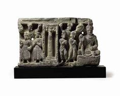 A gray schist relief of Buddha Gandhara, 2nd/3rd Century The Buddha seated at right with his right hand in abhayamudra and the left clutching the folds of his sanghati, his face with pensive downcast eyes, the hair in wavy locks pulled over the ushnisha, with three attendant figures below a frond of leaves to his right, a column in a niche at center and three more attendant figures at far left, all dressed in flowing robes with finely carved folds 12¾ in. (32.4 cm.) wide