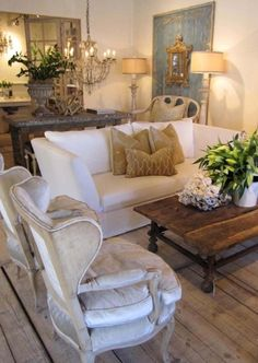 Old weathered coffee table, white couch and chairs, large chandelier, I love all of it! This is my style