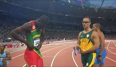 In a 400m qualifying heat, Grenada's Kirani James asks Oscar Pistorius to exchange jersey nametags.  19 year old James would later win Grenada's 1st Olympic medal - gold