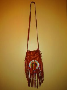 Rustic Brown Bead and Tassel Leather Purse These rustic brown beaded leather bags with tassels will free the wild child inside you. Drawstring to close, and a phone pouch inside, this soft leather purse will give you the elegance you are looking for while still showing off your carefree inner youth.   Height: 10 inches Width: 8 1/2 inches  *Product of Indonesia