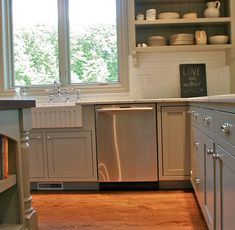 white subway tile backsplash gray painted recessed panel cabinetry oak hardwood flooring. could we morph out kitchen into a variation of this???