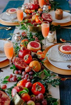 Table with autumn fruit and veggies: blood oranges, persimmons, pomegranates, garlic, heirloom tomatoes, olive leaves, willow eucalyptus and seeded eucalyptus