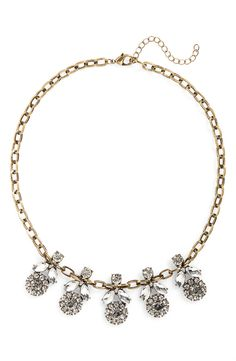 Twinkling floral medallions dress up this antiqued goldtone necklace for a sweet, vintage-inspired statement.