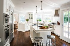 Exquisitely appointed oddly shaped kitchen features two Currey & Co Vitrine Pendant Lights hung above a White Macauba Quartz countertop fitted with a stainless steel sink and Kohler Artifacts Faucet and accenting a white island seating two Crate & Barrel Spin Swivel Backless Counter Stools.