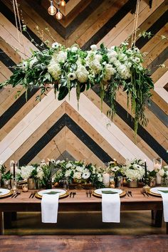 """Guys, how rad is this """"urban tropical"""" wedding concept? It has so many of our fave elements all wrapped up in one: lush greenery (see above!), crisp whites, not to mention the sweet geometric wood pan"""