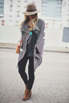 Black blouse with stylish long cardigan and black casual jeans and brown leather hand bag and brown warm leather heels boots and cool cap