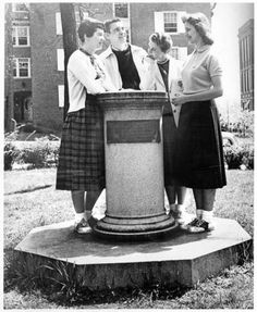 Sundial with four students posing, 1950s :: Ohio University Archives